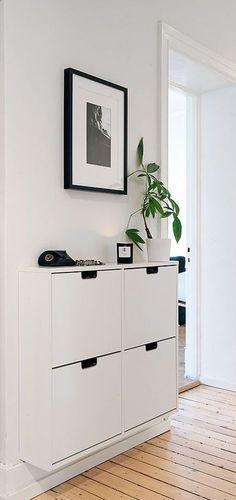decoração de hall de entrada com aparador armázio com planta e quadro preto e branco: