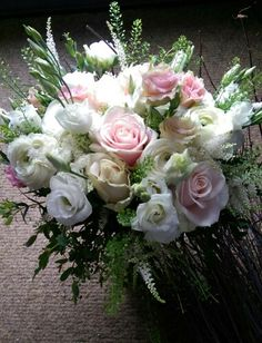 Hand tied bridal bouquet of white ranunculas, sweer avalanche roses, astilbe and lisianthus. Designed by Enchanted Florals in Glastonbury.