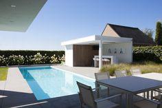 Minimalistisch poolhouse in witte crépi in strakke tuin. modern