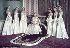 Britain's 27-year-old Queen Elizabeth had been crowned in Westminster Abbey earlier that day, June 2, 1953, and now she poses for photographs in Buckingham Palace. She is wearing the Imperial State Crown and the exquisite Coronation gown designed by Sir Norman Hartnell. The 21ft ermine-trimmed velvet Purple Robe of Estate flows from her shoulders.    She is flanked by her Maids of Honour: six of the country's most blueblooded young women, all single, beautiful and, like the Queen, wearing gow...