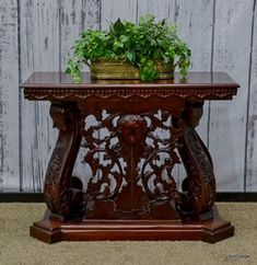 Rosewood console with ornately carved base.