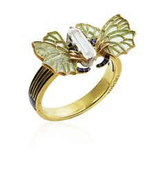 AN ART NOUVEAU DIAMOND AND ENAMEL RING, BY RENÉ LALIQUE. Modelled as two butterflies facing each other, a diamond set between them, the antennae applied with dark blue enamel, the wings applied with green window enamel, circa 1900, ring size 6, mounted in gold. Signed Lalique. #RenéLalique #ArtNouveau #Jewelry #Jewellery #BijouxArtNouveau
