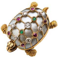 A lovely 18 karat yellow gold Turtle Pin featuring a mother of pearl shell highlighted with small diamonds, rubies and demantoid garnets. Superb surface detail throughout - the head and legs are articulated. Circa 1880s