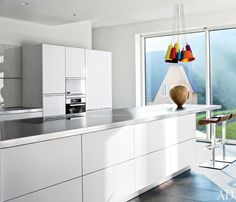 The kitchen's glossy cabinetry and stainless-steel countertops are by Bulthaup, the barstools are by Riva 1920, and the cluster of pendant lights is by Hüttners.