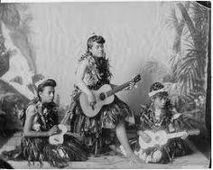 Hawaiian hula dancers with guitar and ukulele photographed in J. J. Williams' photo studio, ca