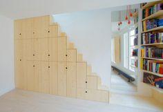 La scala-armadio consente di mantenere un'estetica minimalista nel living. Accanto, una libreria su misura realizzata in legno di larice