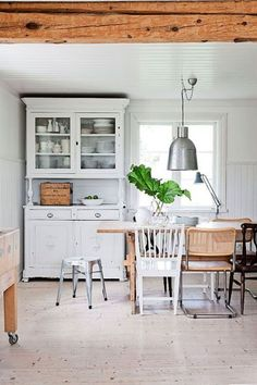 biała kuchnia skandynawska,skandynawska kuchnia w wiejskim stylu,cynowa lampa,drewniany rustykalny stół,biały tradycyjny kredens skandynawski,industrialny stołek,mieszane krzesła przy jednym stole,kuchnia w tradycji skandynawskiej wsi