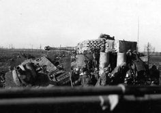 A German Tiger I tank & supporting infantry use a knocked out Russian SU-122 tank for cover...