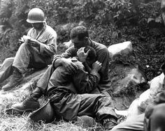 A grief stricken American infantryman whose buddy has been killed in action is comforted by another soldier. In the background a corpsman methodically fills out casualty tags, Haktong-ni area, Korea. August 28, 1950. Sfc. Al Chang.