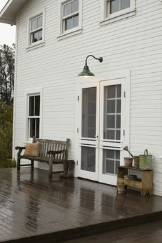 pure white farmhouse with a simple deck and classic lighting (rejuvenation - crane with green dome shade)