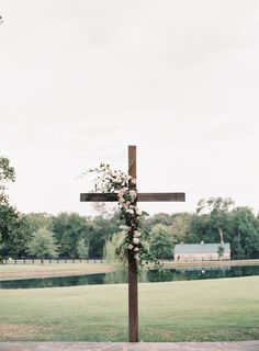 Wooden Cross with Flowers as Wedding Ceremony Backdrop | Photo: Allison Kuhn Photography