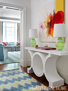 Art by Martin Quen from Deljou Art Group pops above a console table painted a glossy white.  - Photo: Emily Jenkins Followill / Design: Tish Mills