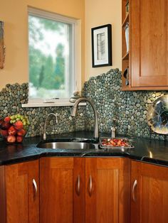 """Although the most common use of these river rock pebbles is actually shower floors, photo stylist Chris Walker and her husband came up with the idea of using them as a kitchen backsplash. They asked their kitchen designer John Petrie, CMKBD, president elect of the National Kitchen and Bath Association, to install it on the walls. """"The one-of-a-kind, free-flowing edges of the pebbles not only mimic the flow of soft teal veins in the dark green soapstone countertops,"""" says Walker, """"but also…"""