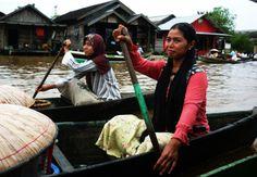 A native Dayak woman paddling her way home - Kalimantan Indonesia