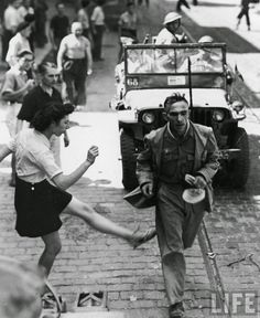 WW II - French woman vents her anger towards a German POW with a kick as he is escorted to a prisoner of war collection center by French soldiers, August 28 1944.