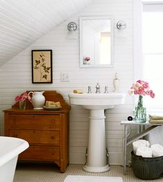 Love the white wood walls, the pedestal sink and antique dresser