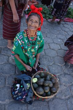 Woman selling avocados on a street in #Guatemala. I love her smile so much.