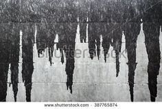 Wet facade wall of a building creating nice abstract dark gray icicle stains. Suitable for background texture as detailed volcanic lava stone wall in black and grey shades.