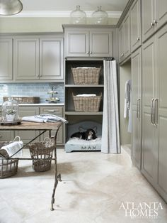 2015 Decorators' Show House & Gardens | Jessica Bradley breathed new life into the dated laundry room, where a rustic table served as a folding table or catch-all between laundry cycles.