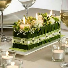 candle centerpiece - 3 candles glass cylinders pushed into green oasis holes , add white Lilly of valley, add Lilly leaves, add ribbon to hold together Floral Centerpieces, Table Centerpieces, Wedding Centerpieces, Wedding Bouquets, Wedding Flowers, Wedding Decorations, Centrepieces, Ikebana, Table Arrangements
