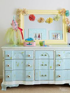 Ashley's childhood dresser, once dark brown, was painted green, then blue, then sanded in places to expose bits of the green paint. A mini dress form found at a flea market becomes a pretty jewelry stand with the addition of paint and a tulle tutu./
