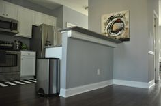 grey and white kitchen with wood laminate floors