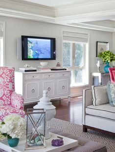 Living room with white walls, white faux bamboo side board, beamed ceiling, white sofa with black piping, wood floor, woven blinds, TV on wall, ottoman coffee table. Pink Ikat upholstered chair.