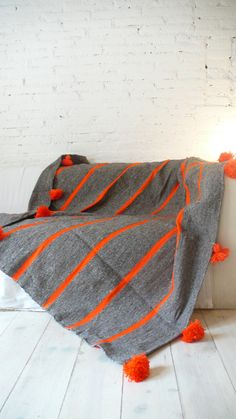 Moroccan POM POM Wool Blanket - Grey with Orange StripesBeautiful Moroccan Blanket Wool, with pompoms on two sides. Handmade in Marrakech. Is perfect for bed cover or sofa.Poms poms are on the top and bottom of the blanket..: Color: Grey with Orange Stripes.: Material: Wool, cotton and acrilic.: Size: 1,40 m wide x 1,45 m long. // 50 in wide x 55 in long. (+/-).: Handmade in MoroccoWash at 30 degrees./. Please allow 12 days before it is ready to ship.