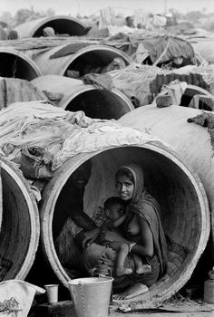 Calcutta, Inde. Des réfugiés du Bangladesh s'installent dans les tuyaux de ciments dans la banlieue. Photographe : Bruno Barbey, 1971 #allaitement