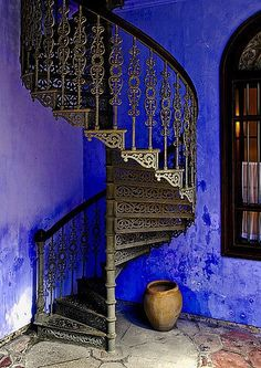 vivid blue walls and spiral staircase