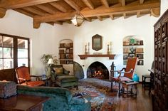 spanish living room, beamed ceiling, stucco fireplace, arched bookshelves, spanish colonial revival style