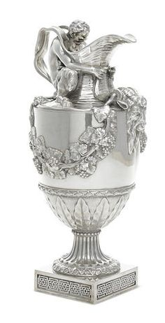 An Edward VII sterling silver wine ewer -  by Goldsmiths & Silversmiths Co., London, 1904; after the model by John Flaxman, Sr. -  'Sacred to Bacchus', in the Renaissance style, with a satyr seated on the shoulder holding ram's mask horns, suspending fruiting vines, weight approximately 121.5oz troy  height 17 in (43cm); length 8 3/4in (22.25cm).