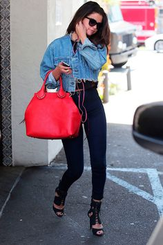 Selena Gomez wears a crop top, skinny jeans, lace-up sandals, cropped denim jacket, and a red satchel bag Cropped Denim Jacket Outfit, How To Wear Denim Jacket, Jean Jacket Outfits, Cropped Shirt, Selena Gomez Daily, Selena Gomez Outfits, Selena Gomez Style, Mode Outfits, Fashion Outfits