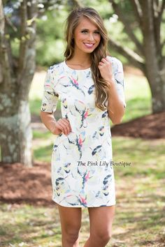 o on an adventure in this beautiful floral dress! It features print in yellow, pink, red, blue, black, light grey, and white, has shorts sleeves, and a zipper in the back!
