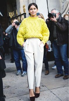 Miroslava Duma wears a cable knit yellow sweater, high-waisted trousers, and platform pumps