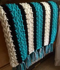 This arrowhead striped crochet blanket pattern features teal and white stripes separately by rows of black, making this a standout pattern