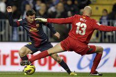 El delantero argentino del Barcelona Lionel Messi consigue el primer gol para su equipo tras regatear al guardameta argentino del Málaga, Willy Caballero