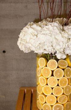 Beautiful and easy summer centerpieces with fresh lemons! Trick is to use a smaller vase inside the larger one to hold the lemons in place.