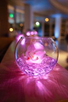 LED light, gel crystals and flower inside a fish bowl. Nice centrepiece idea