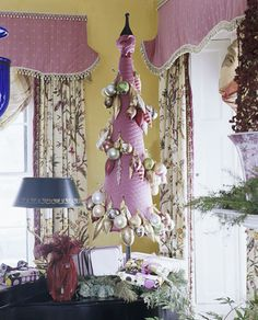 Styrofoam tree covered in fabric with groups of ornaments pinned to it. Easy peasy.