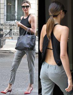 Si te puedes permitir darle un toque sexy a tu outfit de trabajo, ficha este estilismo de Miranda Kerr con un top negro con espalda al aire, pantalones de cuadros en blanco y negro, salones rojos para dar color y bolso de piel negro