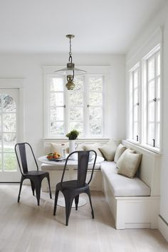 A bright dinning nook with a retro pendant light, metal chairs and a bench