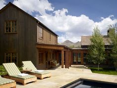 Stain or concrete board exterior with covered porch for rain. Walker-Warner Architects - BIG WOOD RIVER