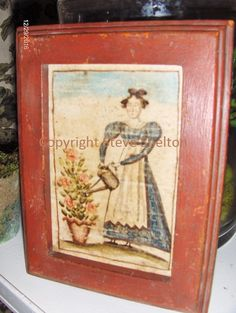 """Watercolor by Steve Shelton: """"Lady in her Garden"""". 1830's style Lady watering her favorite, potted flower. Housed in a crusty, red painted frame. 4 3/4"""" X 6 1/4"""". Contact me for details."""