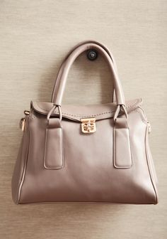 "Smooth Travels Turnlock Satchel 49.99 at shopruche.com. Sophisticated and polished, this structured satchel in taupe is a ladylike addition to your style with gold colored hardware, a unique turnlock closure, and a roomy interior. Includes an optional shoulder strap.14"" L x 11"" H x 5.5"" W, -6"" strap drop, -1 interior zipper pocket, -2 interior organizer pouches, -1 exterior zipper pocket, ,"
