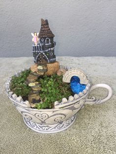 Miniature Fairy Garden - KITTY KASTLE TEA CUP where a girl fairy can be seen on the balcony of her castle and her black kitty is on the first rock step to the castle.