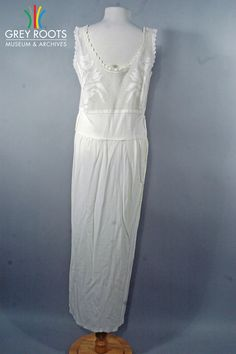 A long, cream-coloured, sleeveless crepe(silk) dress which features belt-loops and a crocheted yolk. The neckline is scalloped with a cream-coloured ribbon threaded through it. Grey Roots Museum & Archives Collection.