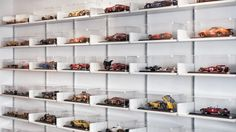 "Clean white shelves and acrylic covers create a striking contrast with this collection of ""as-raced"" model cars."