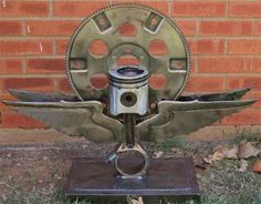 Sculpture created from a salvaged flywheel, piston and rod.  The wings were fabricated from scrap sheet metal.