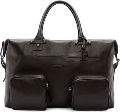 """Unstructured grained leather duffle bag in black. Gunmetal-tone hardware. Rolled leather carry handles with raised square studs. Zippered closure at top with pin-buckled straps at either end. Two zippered patch pockets and raised metal logo at bag face. Zippered pocket at interior compartment. Fully lined in black textile. Tonal stitching. <br><br> Measures approx. 18"""" length x 12"""" height x 10"""" width."""